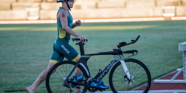 triathlete running with bike