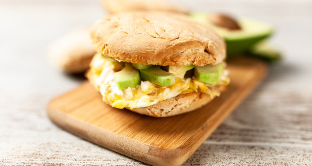 bread with egg and avocado in a chopping board